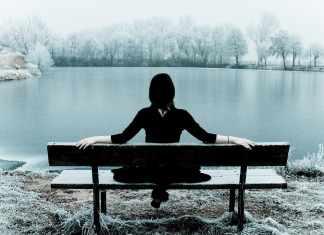 kobieta w czarnej sukni siedząca tyłem na ławce na tle wody i krajobrazu zimowego