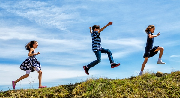 kids running and leaping on hillside