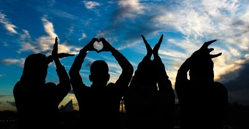 four people spell love with their hands