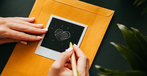 woman drawing heart on large envelope