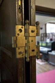 居間とロビーを仕切る扉は両折山戸の金具によって前後どちらにも開閉するようになっています。
