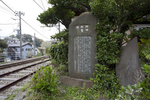 江ノ電線路脇、潮風香る地にあります。隣に立つ歌碑は、戸川稲村のもの。