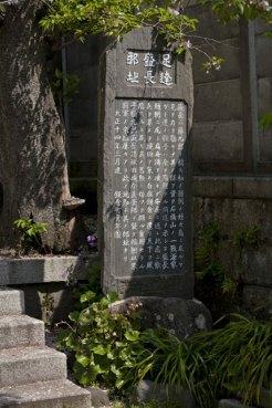 海に近い森に佇む甘縄神明神社の境内にある、安達盛長邸跡の石碑。