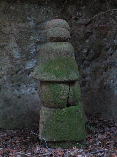 日月やぐらのとなりにあるやぐらの石塔。風雨にうたれてなだらかになった形。