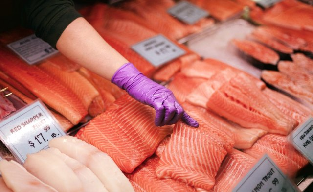 Person pointing at raw salmon at a seafood market