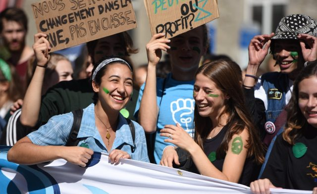 Youth behind smiling behind banner at 2019 youth climate march in Montreal