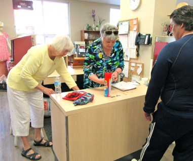 Thrift Shop volunteers Arlene & Fliss. serve a customer.