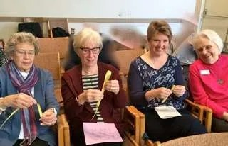 Bonnie, Pat, Jennifer and Mary Ann folding their palm leaves.