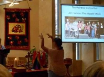"""Rachel, directing the KUC choir with guests from the Pride choir, in """"The Rainbow Connection"""" from """"The Muppet Movie"""" by Jim Henson."""