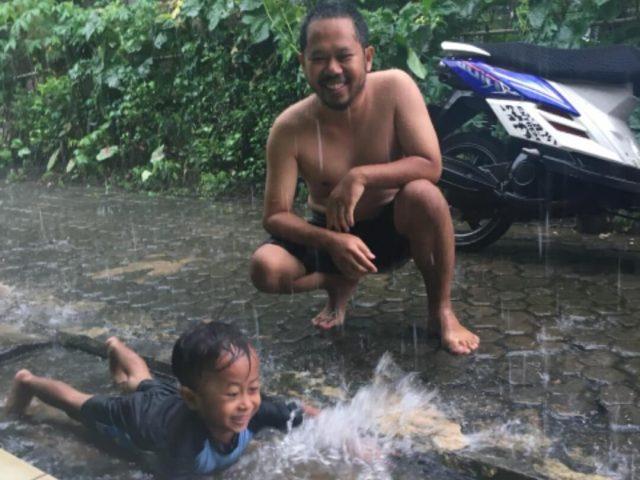 ayah dan anak mandi hujan