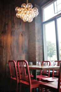 Material palette of stained old pine, exposed brick and the all time classic red 'navy' chairs