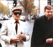 """In the photo, Catholic priest Gerald Ridsdale (left, in sunglasses and hat) walks to court, accompanied by his support person (Bishop George Pell, then an auxiliary bishop in Melbourne), when Father Ridsdale was pleading guilty to his first batch of criminal charges in May 1993 for sexually abusing children. But no bishop accompanied the victims, who felt deserted by the church leaders."""