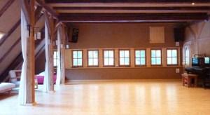 Ein Raum mit Lehmputz, Holzboden, Fensterfront und einem Klavier