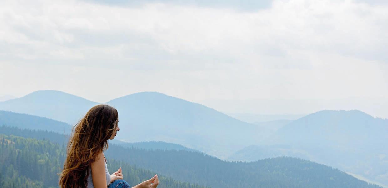 Eine junge Frau meditiert vor einer Kette blauer Hügel im Schwarzwald
