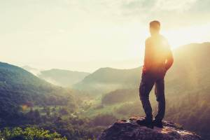 Ein Mann genießt die Weitsicht einer Schwarzwaldlandschaft bei Sonnenaufgang