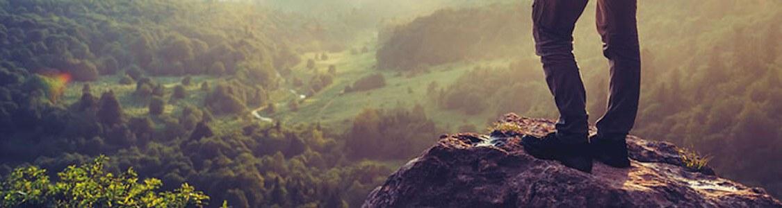 Zwei Beine stehen auf einer Felsnadel vor einem weiten Tal