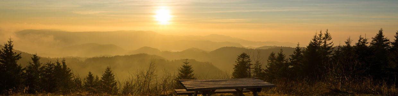 Ein Holztisch auf einer Anhöe mit Panoramablick bei Sonnenuntergang