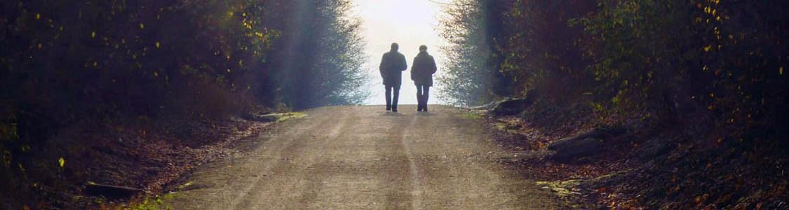 Zwei Menschen gehen einen Weg ins Licht entlang