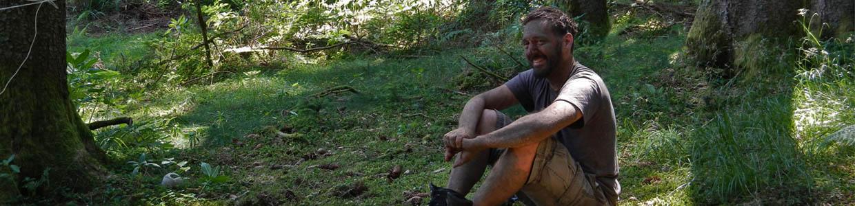 Ein Mann mit Lehm beschmiert hockt lachend im Wald