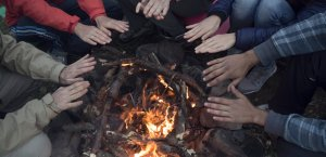 Eine Seminargruppe wärmt ihre Hände an einem gemütlichen Lagerfeuer