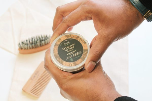 hands opening the beard balm with in the background the comb and the beard brush kanité