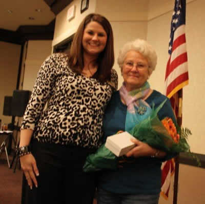 Stephanie McCurdy presenting roses and a gift to retiring historian, Viola Beatty.