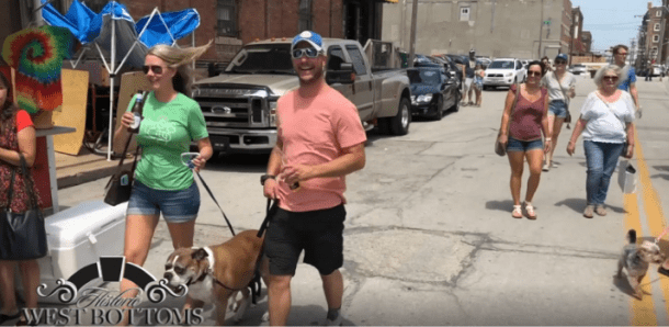 West Bottoms First Friday Festival - man and woman walking dogs outside among the shops