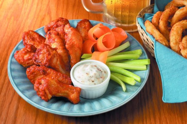 Kansas City Super Bowl Food Deals - plate of chicken wings with celery and blue cheese dressing