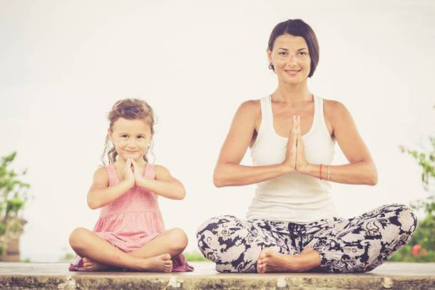 Family yoga at the Overland Park Arboretum - mom and young girl doing yoga outdoors