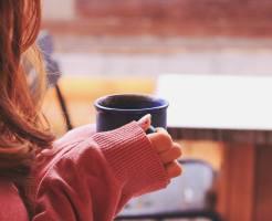 コーヒーを飲もうとする女性の画像