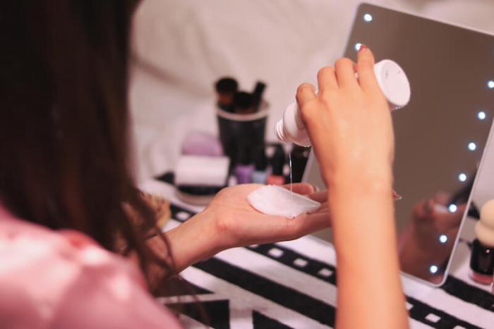 コットンに化粧水を染み込ませている女性