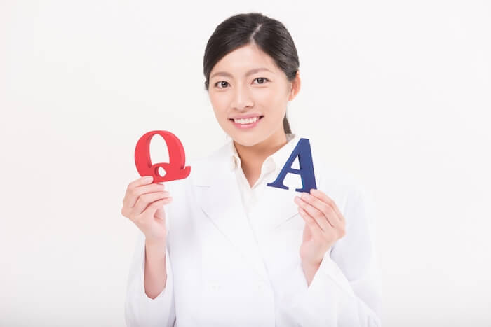QとAの模型を持っている女性の画像