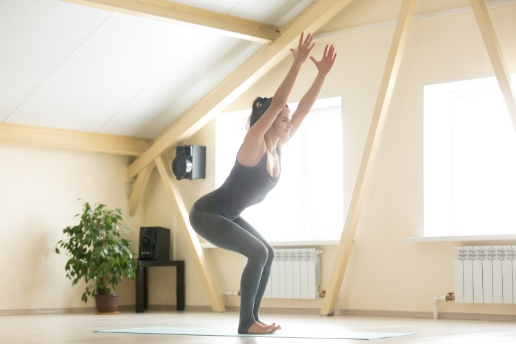 Young attractive woman standing in Utkatasana pose, home interio