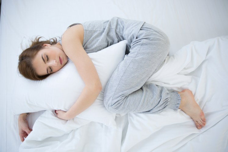 Young woman sleeping in fetal position