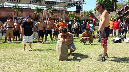 WCC graduate Kawika Meranda (center) prayed to the pohaku (stone) at the WiPCE 2014 event as a traditional challenge kane did during makahiki. The goal was to put the pohaku on his shoulder to show his strength – Courtesy of WCC Peer Mentoring Center