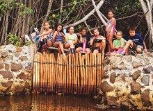 Students from Kiko'u Ko'olau, an after school program, take a break at a makaha (sluice gate) at Paepae o He'eia – Courtesy of Paepae o He'eia