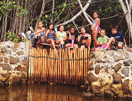 Students from Kiko'u Ko'olau, an after school program, take a break at a makaha (sluice gate) at Paepae o He'eia – Courtesy of Paepae o He'eia