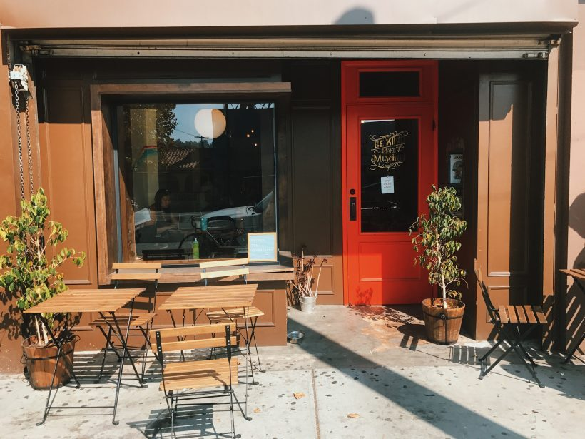 An LA cafe with a red door and wooden chairs out the front.