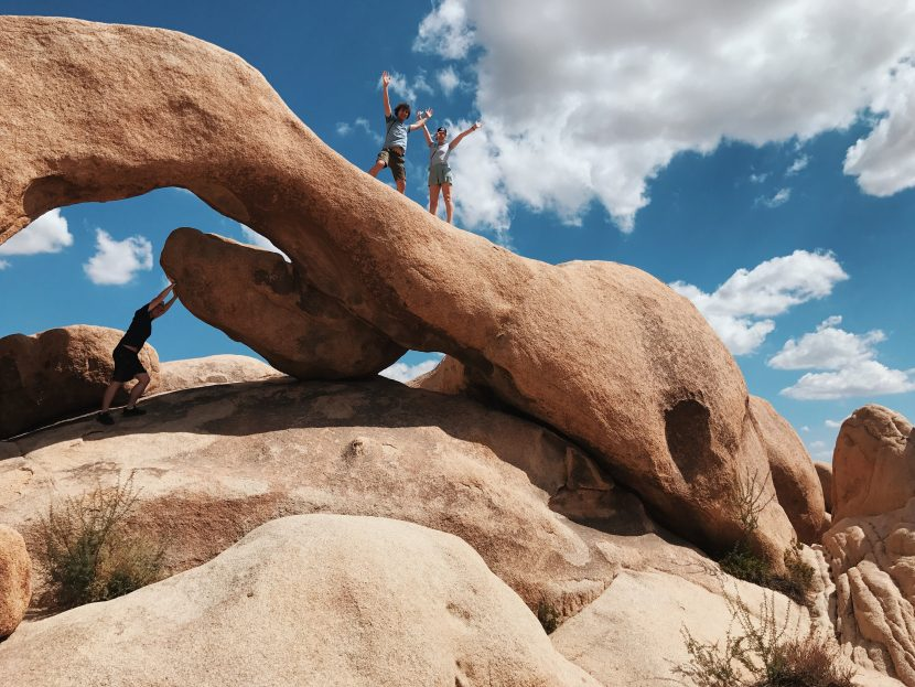 Three people standing on a big granite rock in the shape of an archway.