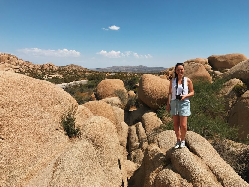 A girl standing on a large granite boulder with the backdrop of desert behind her.
