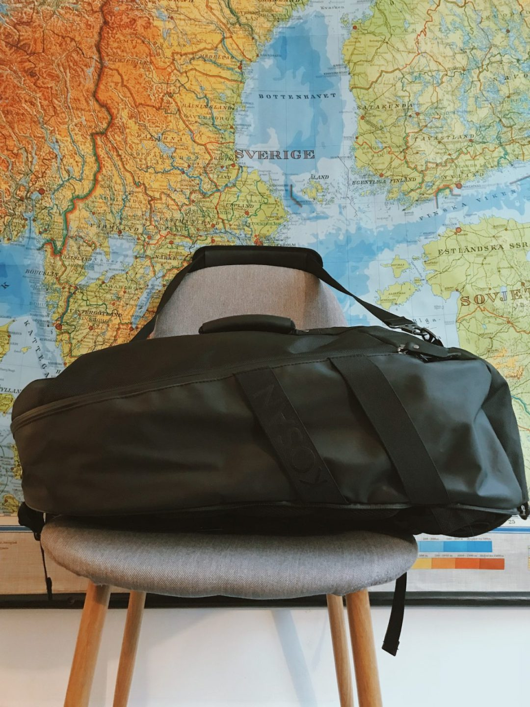 A black hiking backpack on a grey chair