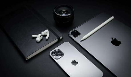 An iphone next to a lense and a macbook. dark image, almost black and white