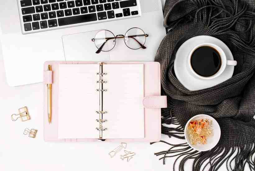 a desk with coffee, glasses, laptop, and a gratitude journal