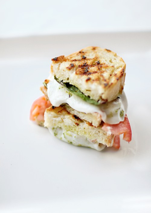 A fresh and easy recipe for a delicious basil, tomato and mozzarella sandwich. The perfect option for a light summer meal! Get the recipe now on Haus of Layne! #EasyMealIdeas #SandwichIdeas #SummerRecipeIdeas #Basil #Mozzarella #Tomato #Pesto #Sandwich