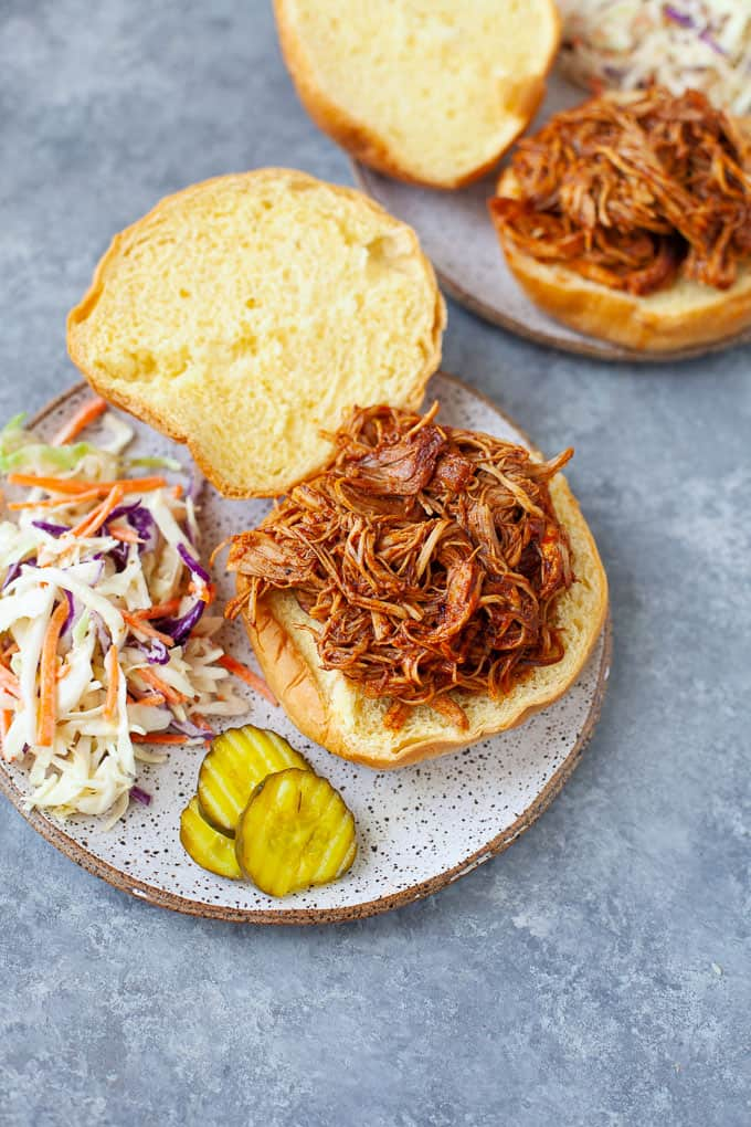 Two plates of BBQ chicken sandwiches with a side of cole slaw