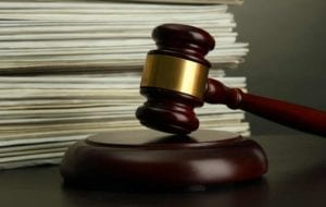 Gavel in front of a stack of court orders (documents)