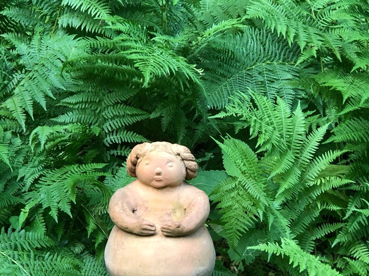 A clay figurine in a strand of ferns.