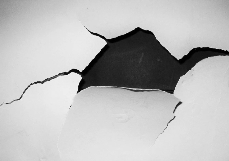 A jagged hole ripped in paper