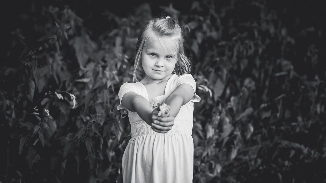Little girl holding out flower.