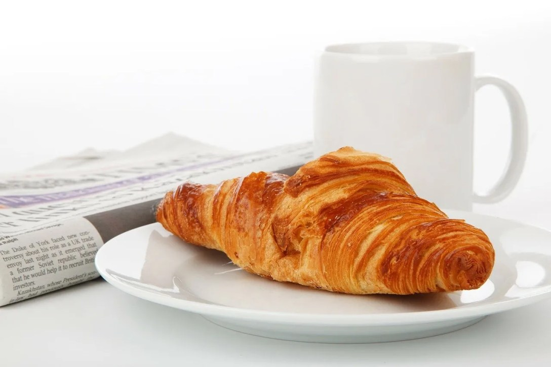 Croissant, coffee and newspaper
